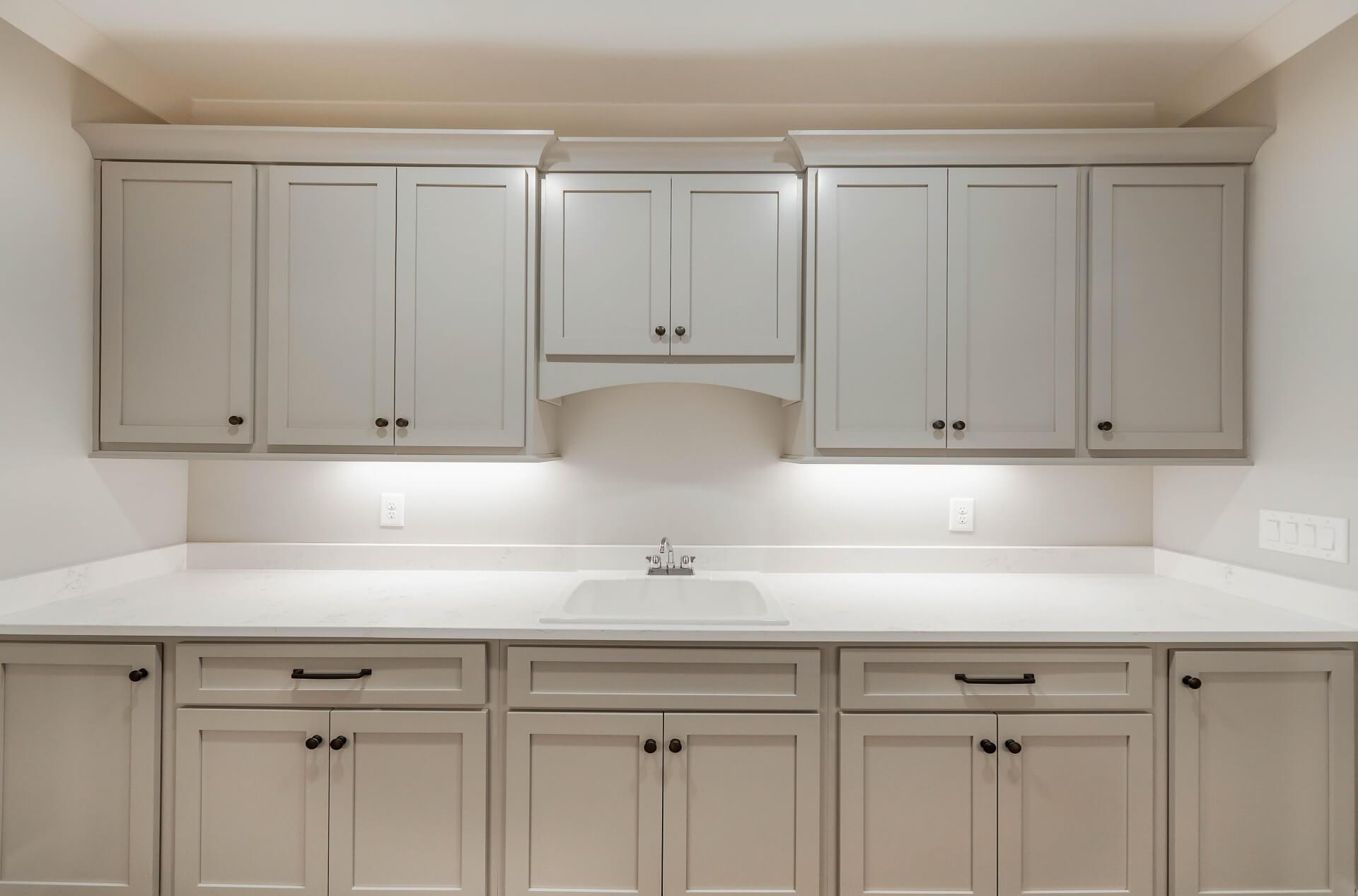Custom-cabinet-laundry-room-shaker-bronze-handles-white-countertops-quartz-1